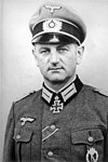 The head and shoulders of a man. He wears a peaked cap and a military uniform and an Iron Cross displayed at the front of his uniform collar. His facial expression is determined; his eyes are looking into the camera.
