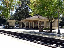An image of a train station, including tracks, platforms, and a shelter.