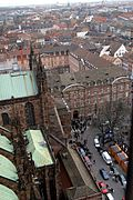 Looking down onto he edge of a cathedral building, with a busy square, in the middle of a city