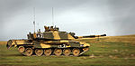photo of a Challenger 2 tank at speed on grassy plain