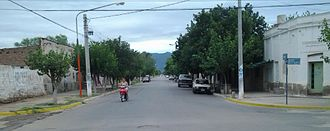 Chamical -  View southwest along Avenida Perón in downtown Chamical. The brushy Sierra de los Quinteros range can be seen in distant background