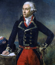 Painting of a determined-looking man who is standing with his left hand on his hip and his right hand on a table. He wears a dark blue double-breasted military coat with red breeches, his hair or wig in the style of the late 18th century, powdered white and curled at the ears.