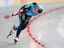 A female speed skater turns around a curve. She is wearing a black and blue body suit.