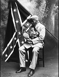 Confederate soldier posing in front of official Confederate battle flag