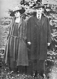 Photographie d'un homme le visage fermé tenant la main d'une femme souriante. Les deux portent une longue veste et un chapeau et la photographie a été prise en extérieur.
