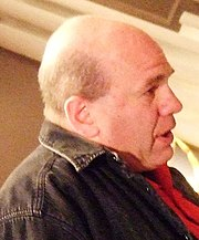 A bald man wearing a black denim jacket and red shirt looking sideways and opening his mouth to speak.
