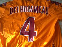 "T-shirt orange avec un flocage ""DELHOMMEAU - 4"" en rouge."