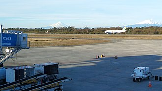 El Tepual Airport - El Tepual International Airport with Calbuco and Osorno volcanoes in the background. A Sky Airline Airbus A-320 jet is also visible.