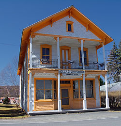 "Old-fashioned, two-story building, with white and orange paint. A sign on the front of the building reads ""ELLA C. EHRHARDT GENERAL STORE."""