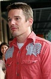Een blanke man met bruin haar en stoppels, gekleed in een rood shirt.