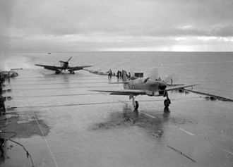 HMS Illustrious (87) - A prototype Fairey Firefly taking off with a prototype Blackburn Firebrand behind it, during deck-landing trials, February 1943