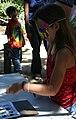 Fairgoer tries her hand at bird bingo (5985889666).jpg