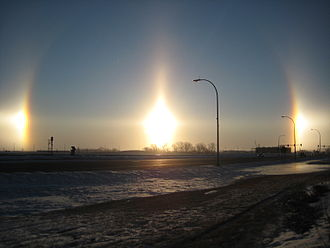 Sun dog - Very bright sun dogs in Fargo, North Dakota. Also visible are parts of the 22° halo (the arcs passing through each sundog), a sun pillar (the vertical line) and the parhelic circle (the horizontal line).