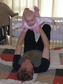 A young father lies on his back on a quilt on the floor. He holds his baby daughter up above him with his arms straight and his hands round her ribcage, the baby has her arms and legs stretched out and arches her back smiling directly at the camera.