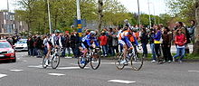 Three road racing cyclists riding in a single file line. Cars follow on the road behind them, and spectators watch from the roadside.