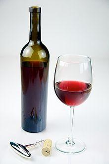 Una bottiglia e un bicchiere contenenti del vino rosso
