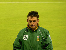 A white man with short dark hair in a green all-weather jacket.  He is standing in front of a large expanse of grass.