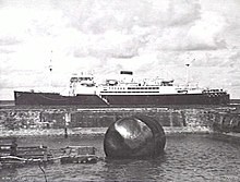 Black and white photo of a large ship anchored off a beach. A damaged buoy is in the foreground of the photo.