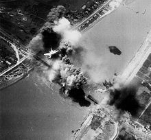 A black-and-white photograph showing an explosion on a railway bridge, with an American bomber flying overhead.