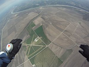 Altimeter - Skydiver in free fall, making use of a hand-mounted altimeter. The analogue face is visible, showing colour-coded decision altitudes. The depicted altimeter is electronic, despite using an analogue display.