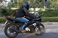 Helmeted rider in motion on Yamaha YZF-R15 side.jpg