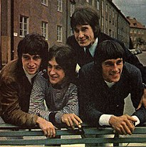 Four smiling young men leaning over the back of a green park bench, a row of three-story-tall residential buildings behind them. The man on the left wears a brown sports jacket and white turtleneck; the man to his left wears a black-and-white-striped pullover shirt; the man to his left (standing straighter, just behind the other three) wears a black suit and tie; the man on our far right wears a black sports jacket and white shirt.