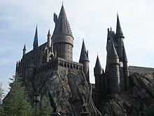 Un château en pierres grises situé en hauteur sur un rocher et hérissé de nombreuses tours pointues