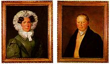 At left, a painted portrait of a woman in a black dress with a frilled hood and ruffled collar. At right, a painted portrait of a man in a black coat wearing a cravat.