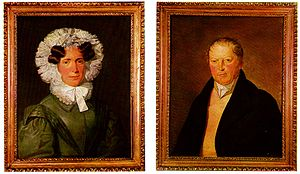 At left, a painted portrait of a woman in a black dress with a frilled hood and ruffled collar. At right, a painted picture of a man in a black coat wearing a cravat.