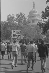 Un manifestant tient au-dessus de sa tête une pancarte où est inscrit «Impeach Nixon». D'autres personnes marchent comme lui en direction du Capitole.