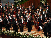 Several dozen musicians in formal dress, holding their instruments, behind a conductor