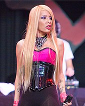 Ivy Queen, performing, looking to her left side.