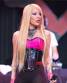 A blonde woman looking to her left, wearing a pink and black–coloured dress and holding a microphone in her left hand.