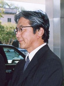 Profile of a middle-aged Japanese man from the chest up wearing a dark suit, blue tie, and glasses. His hair is greying to a silver.