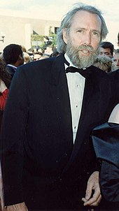 A tall, thin man in his early fifties, with salty-gray hair and a full beard, and wearing a tuxedo.