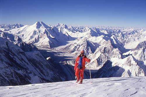 A climber stands in front of a vista of snow-covered mountains