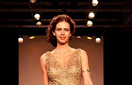 Koechlin walking the ramp in gold dress.
