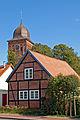 Kleines Fachwerkhaus mit Kirchturm in Gingst (Rügen) (11983700433).jpg
