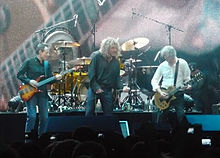 Led Zeppelin onstage: John Paul Jones playing bass guitar, Robert Plant holding a microphone, and Jimmy Page playing guitar. The trio stand in front of Jason Bonham's drum kit.