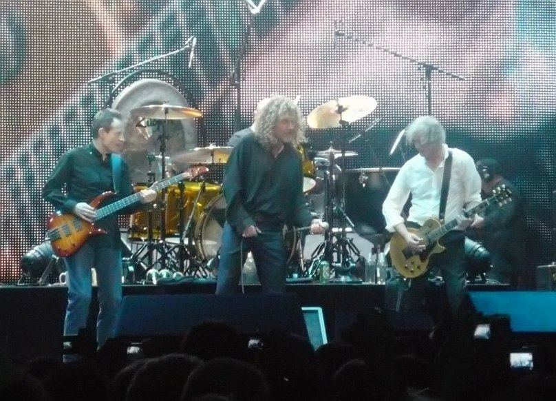 A colour photograph of John Paul Jones, Robert Plant and Jimmy Page performing on stage, with Jason Bonham partially visible on drums in the background