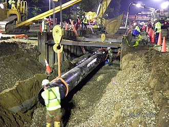Kalamazoo River oil spill - Technicians begin removal of a section of pipe from the Enbridge pipeline oil spill site near Marshall, Michigan