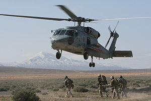 Sikorsky SH-60 Seahawk - A Seahawk hovers during a simulated casualty evacuation as MARSOC operators carry a stretcher.