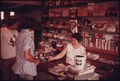 MRS. WARREN BROWN (BEHIND COUNTER) OPERATES THE GROCERY INSIDE THE SERVICE STATION SHE AND HER HUSBAND HAVE OWNED FOR... - NARA - 557686.tif