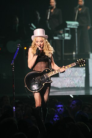 "Human Nature (Madonna song) - Madonna performing ""Human Nature"" on the Sticky & Sweet Tour (2008–09), while playing a black Les Paul guitar"