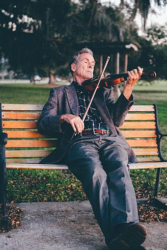 Man playing violin on a park bench. Man Playing Violin on Bench at Park.jpg