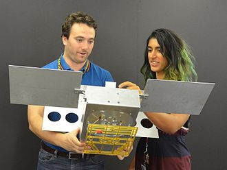 Mars Cube One - Mechanical engineer Joel Steinkraus and systems engineer Farah Alibay, from JPL, holding a full scale model of  Mars Cube One (MarCO)