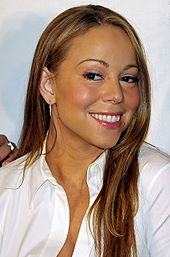 A light haired medium skin colored female smiling. The female has long hair and is wearing a white sleeved shirt that is slightly un-buttoned at the top.