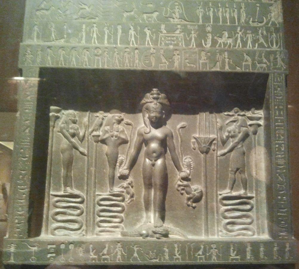 Detail der Metternich Stele, Horus, das Kind steht auf einem Krokodil, zwei Schlangen, zwei Skorpione, einen Löwen und eine Oryx-Antilope haltend, Foto: Eb.Hoop, Wikimedia Commons