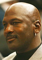 A smiling bald black man wearing a silver earring and herringbone jacket
