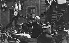 Zwart-witfoto van een man met wit haar, met vlinderdas en driedelig pak, zwaaiend naar de menigte met zijn hoed;  op de achtergrond is een gebouw van de Franse Republiek zichtbaar